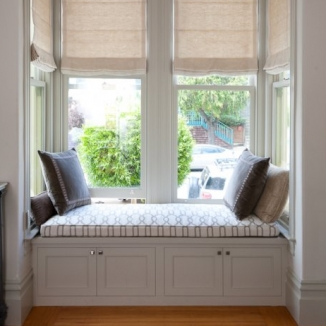 Motorized Roman shades for effortless opening and closing, an indoor/outdoor fabric on the window seat, and gray pillows turn this west facing deep bay into useable space.