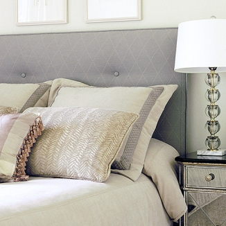A tufted upholstered headboard, shams, and pillows in subtle tones establish the serenity in this San Francisco Noe Valley guest room.