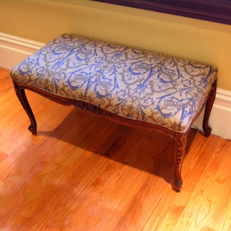 A classic bench is reupholstered to coordinate with the entryway's new color palette.