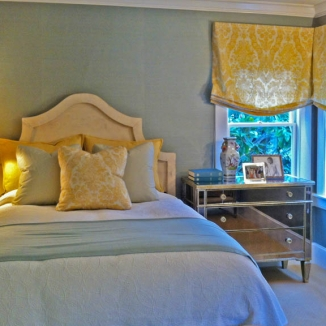 Custom bedding, pillows and window treatments in a bright yellow damask charmingly compliment the blue tones in this feminine bedroom.