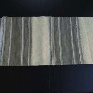 A delicate combination of subtly hued linens of different weights is pieced to create the stripes of this contemporary table runner designed by Jennifer Mobley of Mobley Bloomfield.