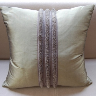 Three individual strips of brushed trim are precisely combined on this sophisticated silk pillow designed by Jennifer Mobley of Mobley Bloomfield.