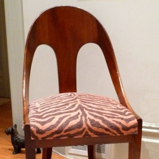 The beauty of the wood and elegant curves in this chair are emphasized by an animal print in complimentary colors.