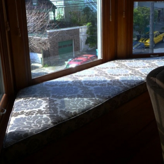 A traditional cut-velvet that is really an indoor/outdoor fabric makes this west-facing window seat cushion as interesting in this Victorian bay as it is durable.