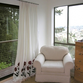 A printed Suzani floral fabric adds a surprising punch of color to these curtains in an all white San Francisco bedroom. The finish on the rod and rings were selected to coordinate with the window frames.