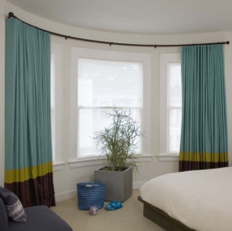 Bold, colorful blackout curtains on a single curved rod over sheer curved Conrad shades will be perfect now and for years in this San Francisco kid's room.