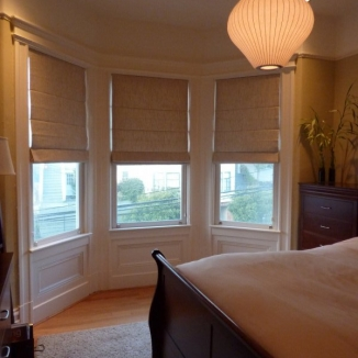 Simple yet expertly tailored flat-front Roman shades in this bay window have extra thick lining to block noise and preserve the Zen-like calm and luxury of this Russian Hill guest room.