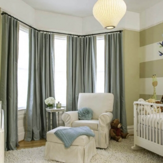 A layered treatment in soft tones is used for optimal light and noise control in this Noe Valley nursery. Harsh daylight is softened with light-filtering shades, while the blackout curtains and hardware were designed and fabricated to minimize street noise.