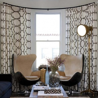 A bold contemporary print fit perfectly in this San Francisco living room bow window designed by interior designer Lisa Bakamis.