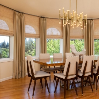 Floor to ceiling draperies on an angled rod are paired with natural woven shades hung behind the rod to emphasize the high ceiling while subtly preserving the window arches in this sophisticated Hillsborough dining room.