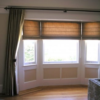 Light is easily controlled with this layered treatment in a shallow bay window. The crisp Roman shades can be raised or lowered for maximum or filtered light while the curtains can be drawn for complete blackout.