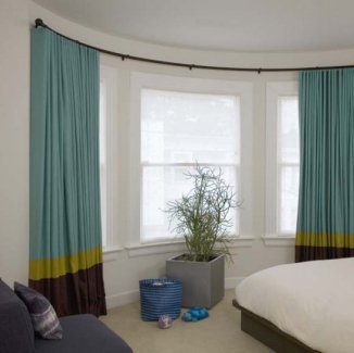 Bold, colorful blackout curtains on custom curved rods over specially curved Conrad shades enable great light control for nap time in this timeless San Francisco kid's room.