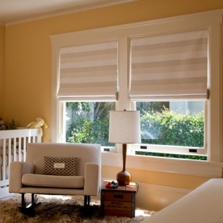 A great horizontal stripe on these blackout lined Roman shades keeps this Piedmont Terrace nursery decidedly modern.