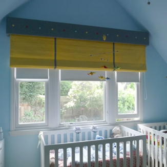 An extra-wide upholstered cornice and coordinating shade playfully unifies three windows and darkens the room in this Noe Valley, San Francisco nursery for twin boys.