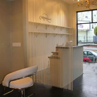A shimmery faux pearl curtain separates the reception desk while allowing natural light and the outside view to filter through at the station in this upscale San Francisco hair salon.