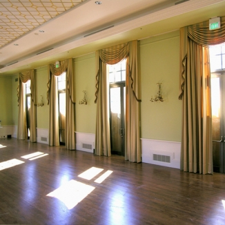 Formal swags with fringed tails and classic pleated draperies dress up the ballroom in this Peninsula country club.