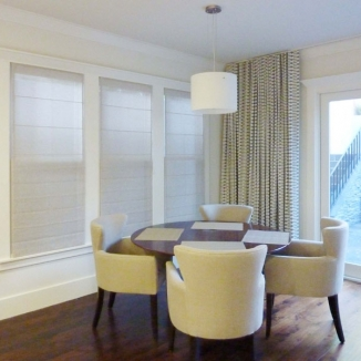 Sheer Roman shades provide privacy for a family room on a set of windows that look out on the neighboring property.