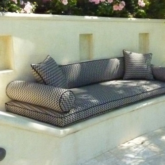 Mediterranean style lounge area gets style and comfort with indoor outdoor fabrics on the cushions and pillows.