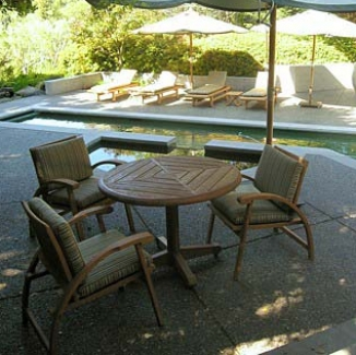 Poolside dining chairs and chaise lounges get comfortable with cushions in a crisp stripe of hard wearing, low maintenance fabric by Alaxis.
