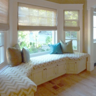 Stitch fabricated Roman shades in beautiful Windochine as well as the window seat and contrasting pillows in this sophisticated San Mateo family room that is light, stylish, and practical.