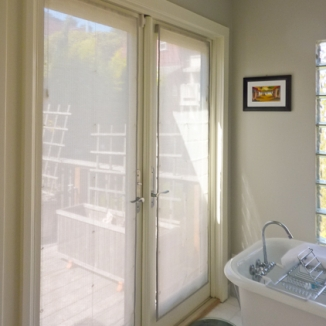 Roman shades made up in a delicate woven sheer are banded in a raw silk matched to the marble in this garden facing master bath in Noe Valley.