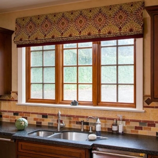 The perfectly scaled pattern of this large Roman shade coordinates beautifully with the Italian tile and custom cabinetry in this expansive Hillsborough kitchen.