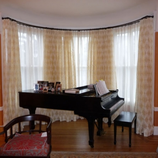 Two layers of sheer fabrics in the room's color palette provide a stunning backdrop while helping protect the piano from sun.