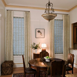 A subtle pattern in the curtains combine with a subtle stripe in the Roman shades to update and emphasize the quiet tones of the traditional décor in this San Francisco Hayes Valley dining room. The finish of the rods and rings echo the finish in the chandelier for a well-coordinated look.