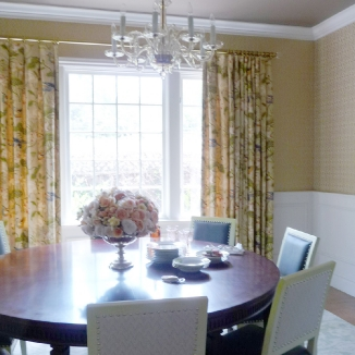 A traditional print in muted colors provide a soft backdrop in this traditional, elegant dining room. Gold-toned rod and rings and glass finials reflect the room's traditional elements.