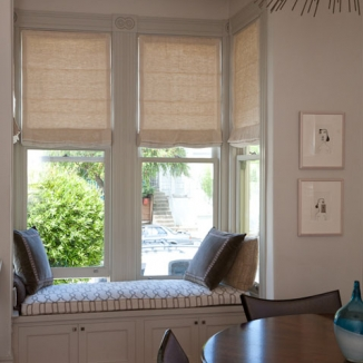 Roman shades over built-in window seating with hidden storage expand the useable space in this San Francisco Victorian dining room bay window.
