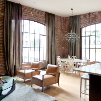 Oddly placed sprinklers and exposed pipes are carefully camouflaged with dark toned draperies that preserve the arch shaped windows, emphasize the brick, and add softness to the room. They provide privacy and protect the floors and furnishings in this sunny SOMA San Francisco location.