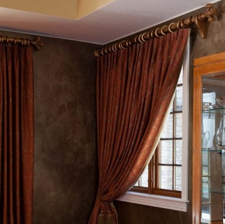 Lovely orange and gold toned fabric curtains heighten the drama of this Hillsborough dining room