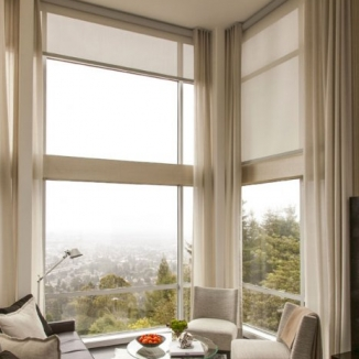 A stunning view is preserved while the furnishings are protected on the sunniest days with motorized floor-to-ceiling solar shades that significantly cut heat and glare. Grey sheers in a Pollack fabric beautifully frame the many two-story high windows in this amazing Berkeley Hills home.