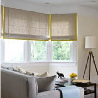 Yellow grosgrain banding on the Roman shades in the living room beautifully coordinate with the dining room shade.