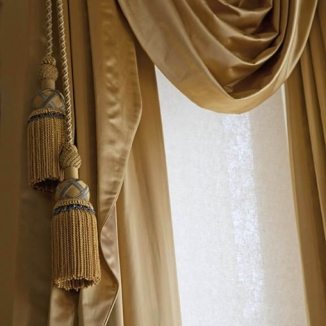 Unable to find the perfect colors for the trim, Stitch instead commissioned Samuel & Sons of NY to make large custom tassels that echo the gray tones of the room's upholstery and ceiling.